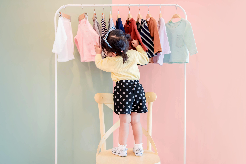 Little girl choosing a shirt